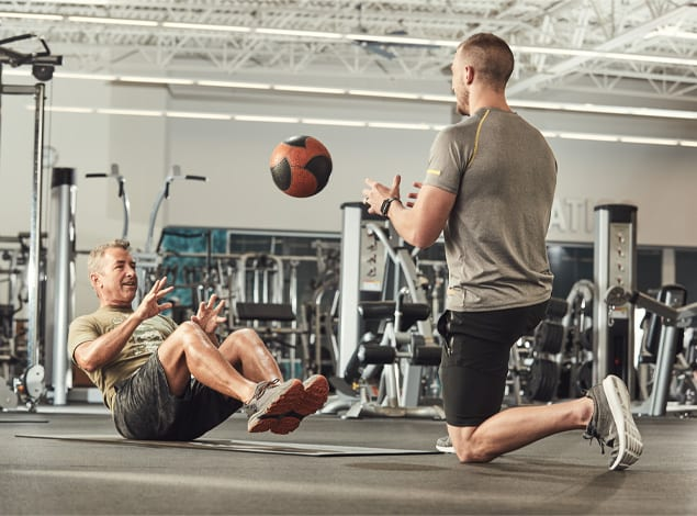 two men doing strength training at Richmond Golds Gym